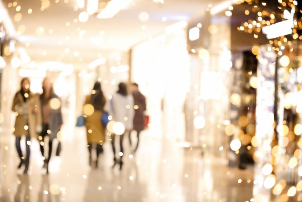 people shopping in mall surrounded by holiday lights