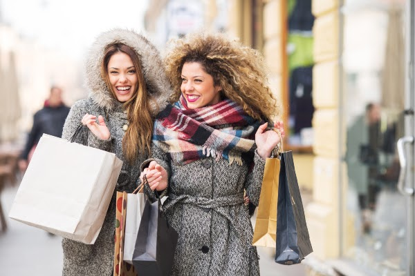 two women smiling and shopping in the winter