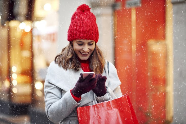 woman reading news on her phone while shopping in the winter
