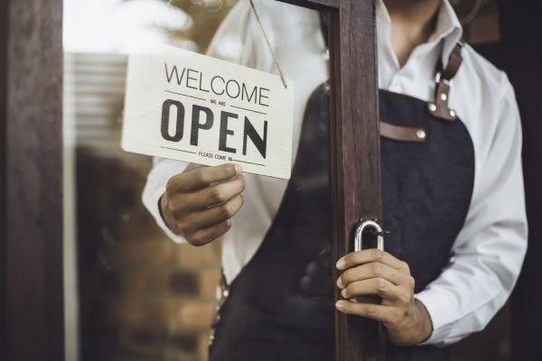 "man flipping ""open"" sign on store front door"